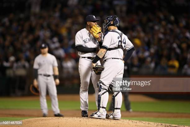 Luis Severino of the New York Yankees talks to catcher Gary Sanchez after throwing a wild pitch against the Oakland Athletics in the first inning at...