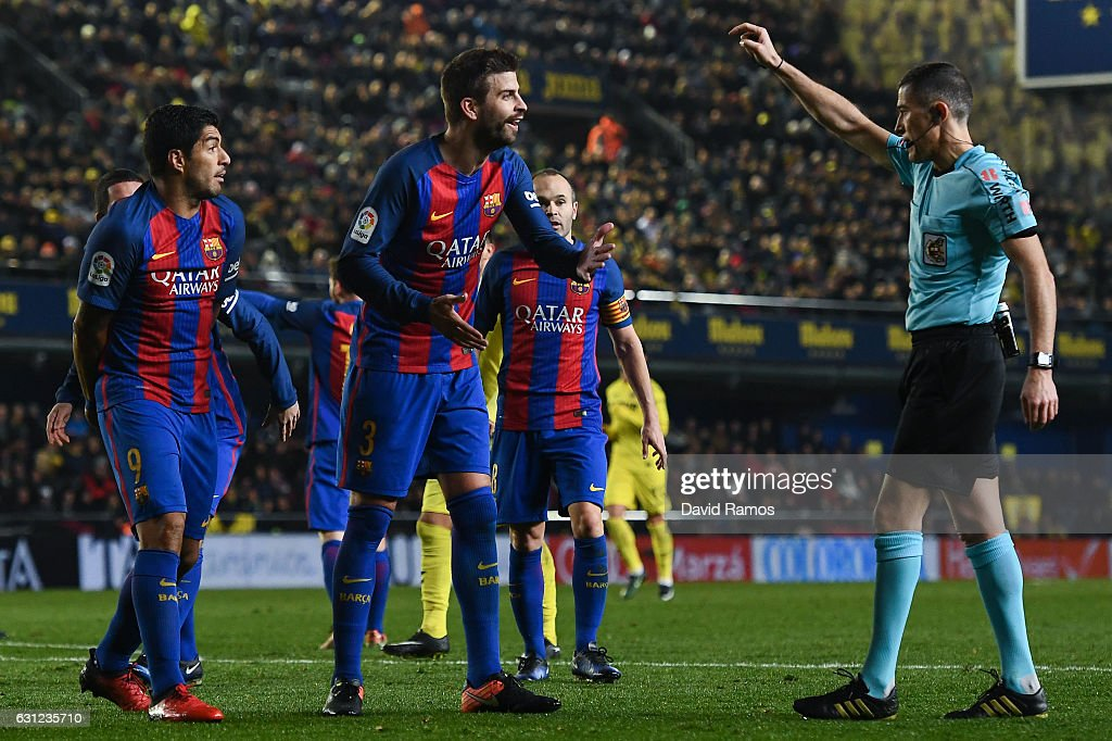Luis Suarez (L) and Gerard Pique of FC Barcelona argue with the referee Ignacio Iglesias Villanueva during the La Liga match between Villarreal CF and FC Barcelona at Estadio de la Ceramica stadium on January 8, 2017 in Villarreal, Spain.
