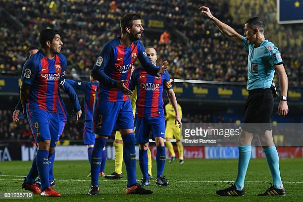 Luis Suarez and Gerard Pique of FC Barcelona argue with the referee Ignacio Iglesias Villanueva during the La Liga match between Villarreal CF and FC...