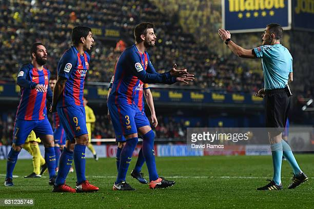Luis Suarez and Gerard Pique of FC Barcelona argue with the referee Ignacio Iglesias Villanueva during the La Liga match between Villarreal CF and FC...