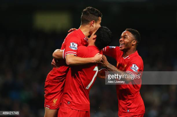 Luis Suarez and Raheem Sterling of Liverpool congratulate goalscorer Philippe Coutinho during the Barclays Premier League match between Manchester...