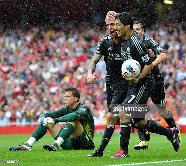 Luis Suarez and Raul Meireles of Liverpool celebrate the opening goal as Wojciech Scezney of Arsenal shows his dejection during the Barclays Premier...