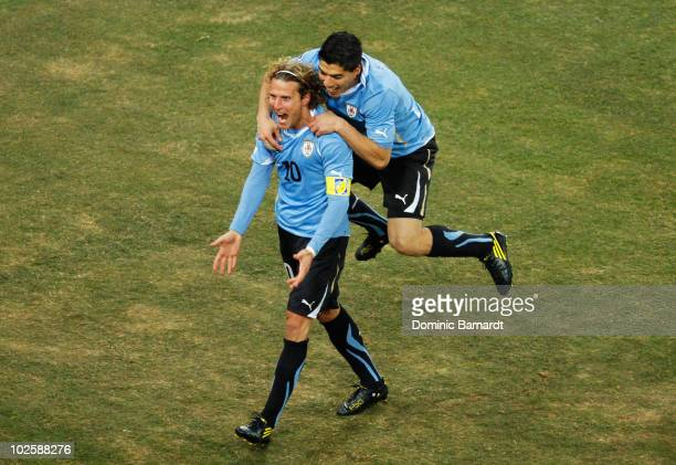 Luis Suarez celebrates with Diego Forlan of Uruguay celebrates after he scored his team's first goal from a free kick during the 2010 FIFA World Cup...