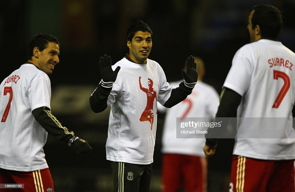 Luis Suarez (C) jokes with Jose Enrique (R) and Maxi Rodriguez (L) of Liverpool as the teams warm up ahead of the Barclays Premier League match between Wigan Athletic and Liverpool at the DW Stadium on December 21, 2011 in Wigan, England.
