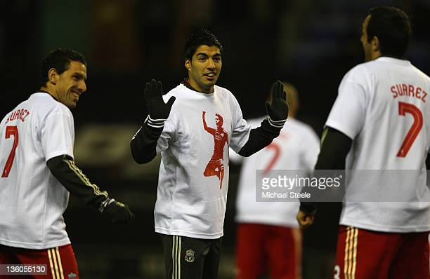 Luis Suarez jokes with Jose Enrique and Maxi Rodriguez of Liverpool as the teams warm up ahead of the Barclays Premier League match between Wigan...