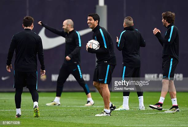 Luis Suarez jokes with Lionel Messi during a Barcelona training session ahead of their UEFA Champions League quarter final first leg match against...
