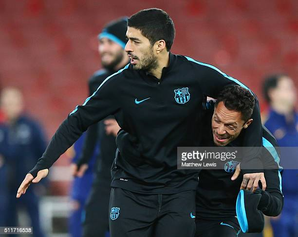 Luis Suarez jokes with team mate Adriano during a FC Barcelona training session ahead of their UEFA Champions League round of 16 first leg match...