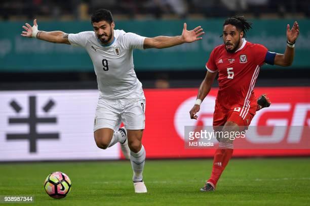 Luis Suarez left of Uruguay national football team kicks the ball to make a pass against Ashley Williams of Wales national football team in their...