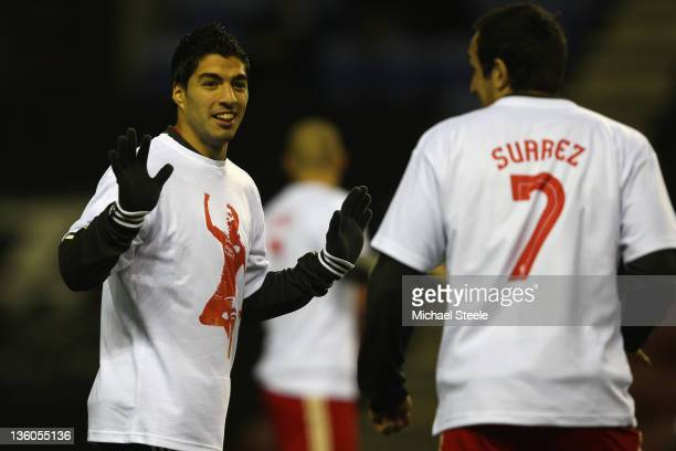 Luis Suarez looks towards Jose Enrique of Liverpool as the teams warm up ahead of the Barclays Premier League match between Wigan Athletic and...