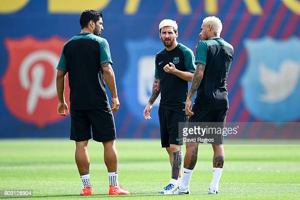Luis Suarez Neymar Jr and Lionel Messi of FC Barcelona talk during a training session ahead of their UEFA Champions League Group C match against...
