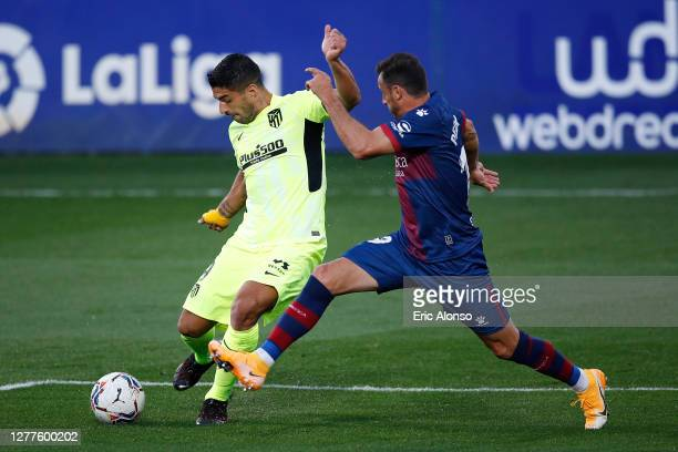 Luis Suarez of Atletico de Madrid shoots under pressure from Pedro Lopez of SD Huesca during the La Liga Santander match between SD Huesca and...