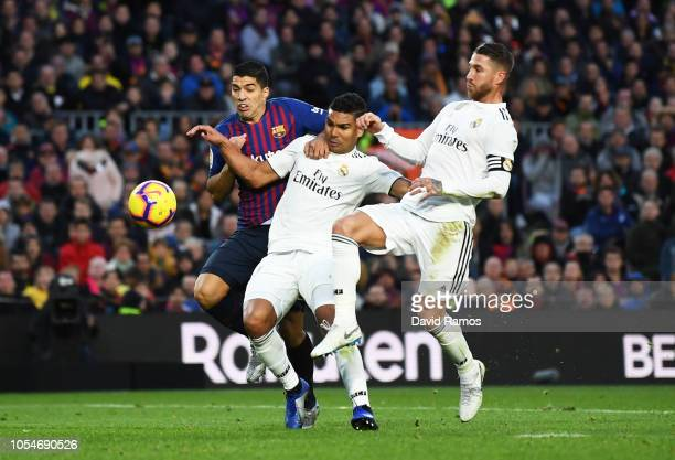 Luis Suarez of Barcelona battles with Casemiro and Sergio Ramos of Real Madrid during the La Liga match between FC Barcelona and Real Madrid CF at...