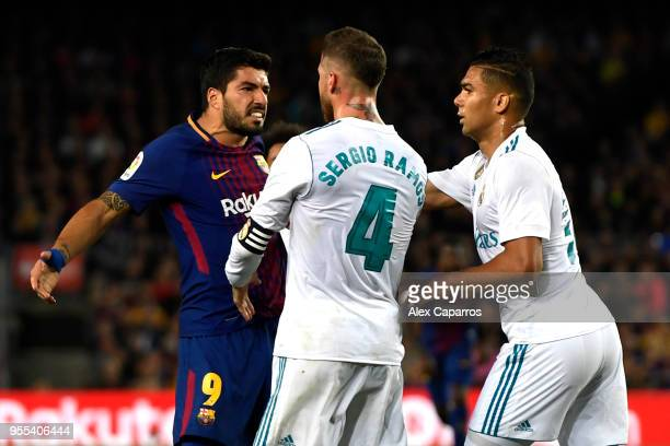 Luis Suarez of Barcelona clashes with Sergio Ramos and Casemiro of Real Madrid during the La Liga match between Barcelona and Real Madrid at Camp Nou...