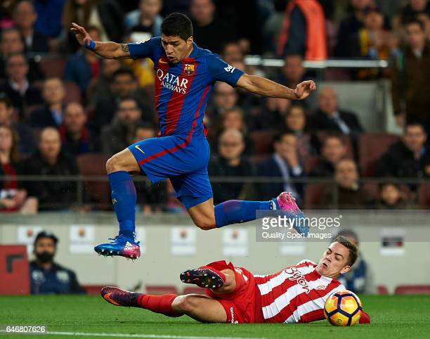 Luis Suarez of Barcelona competes for the ball with Juan of Real Sporting de Gijon during the La Liga match between FC Barcelona and Real Sporting de...
