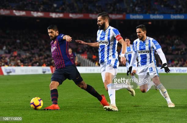 Luis Suarez of Barcelona evades Dimitris Siovas and Recio of Leganes during the La Liga match between FC Barcelona and CD Leganes at Camp Nou on...