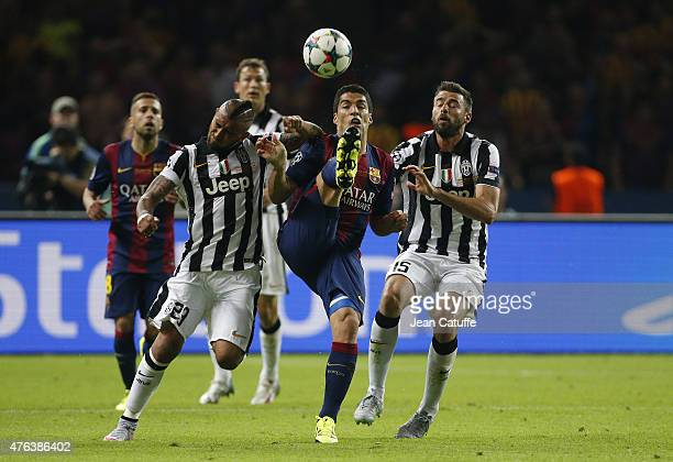 Luis Suarez of Barcelona in action between Arturo Vidal and Andrea Barzagli of Juventus Turin during the UEFA Champions League Final between Juventus...