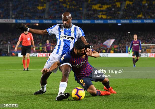 Luis Suarez of Barcelona is challenged by AllanRomeo Nyom of Leganes during the La Liga match between FC Barcelona and CD Leganes at Camp Nou on...