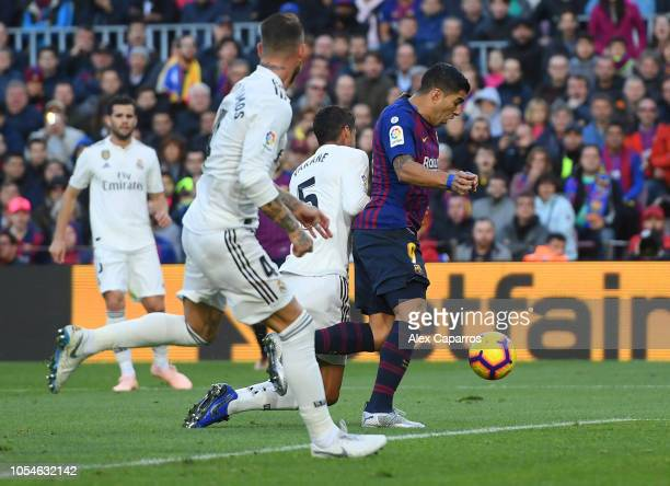 Luis Suarez of Barcelona is challenged by Raphael Varane of Real Madrid with a penalty awarded following a VAR decision during the La Liga match...