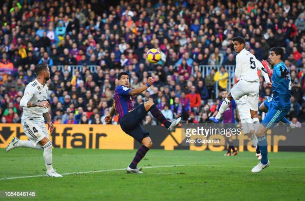 Luis Suarez of Barcelona is foiled by Raphael Varane and Thibaut Courtois of Real Madrid during the La Liga match between FC Barcelona and Real...
