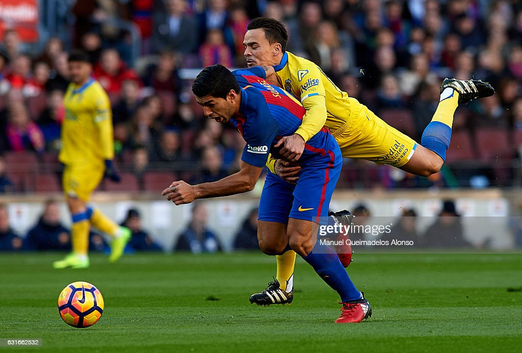 Luis Suarez (L) of Barcelona is tackled by Roque Mesa of Las Palmas during the La Liga match between FC Barcelona and UD Las Palmas at Camp Nou Stadium on January 14, 2017 in Barcelona, Spain.