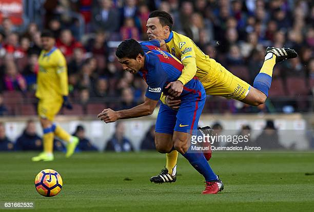 Luis Suarez of Barcelona is tackled by Roque Mesa of Las Palmas during the La Liga match between FC Barcelona and UD Las Palmas at Camp Nou Stadium...