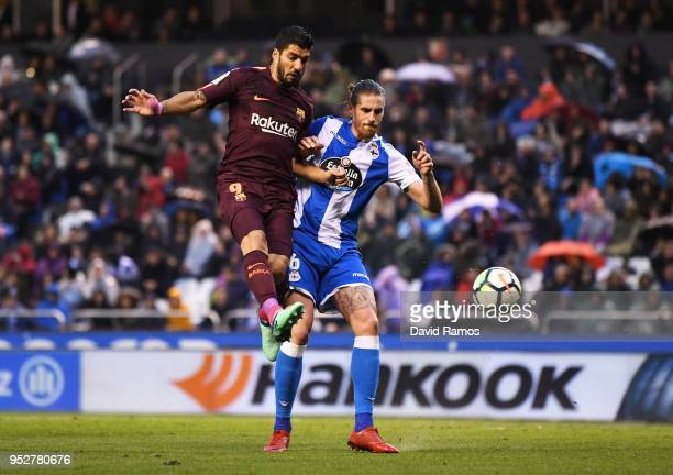 Luis Suarez of Barcelona jumps for a header with Raul Albentosa of Deportivo La Coruna during the La Liga match between Deportivo La Coruna and...