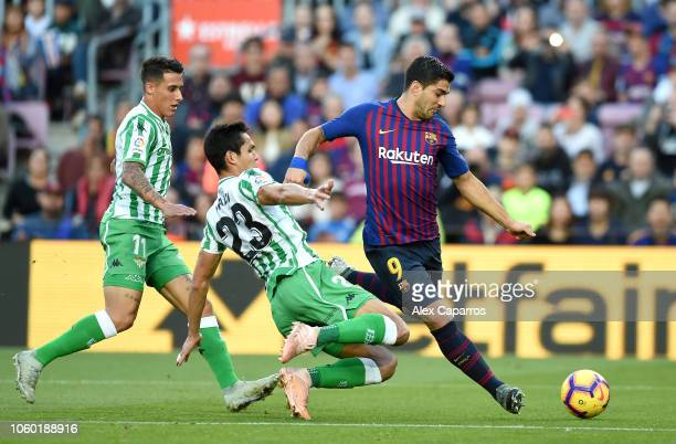 Luis Suarez of Barcelona runs with the ball under pressure from Cristian Tello and Aissa Mandi of Real Betis during the La Liga match between FC...