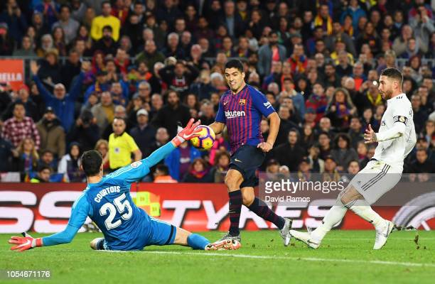 Luis Suarez of Barcelona scores his sides fourth goal past Thibaut Courtois of Real Madrid and completes his hat trick during the La Liga match...