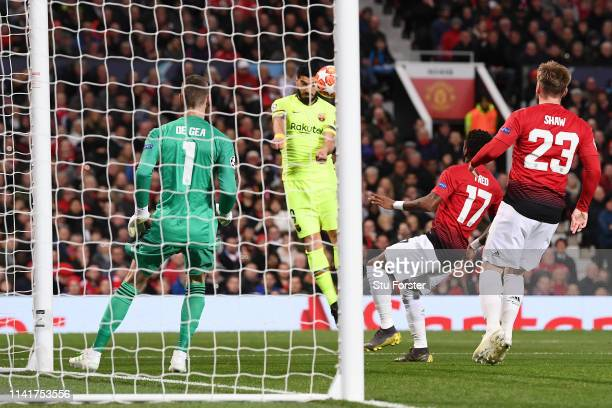 Luis Suarez of Barcelona shoots on goal and sees his shot deflected onto Luke Shaw of Manchester United leading to his team's first goal during the...