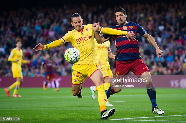 Luis Suarez of FC Barcelona and Igor Lichnovsky of Sporting Gijon compete for the ball during the La Liga match between FC Barcelona and Sporting...