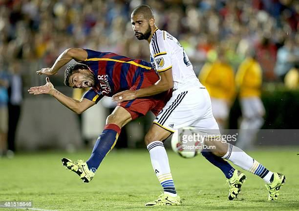 Luis Suarez of FC Barcelona and Leonardo of the Los Angeles Galaxy collide as Suarez tries to get off a shot in the International Champions Cup 2015...