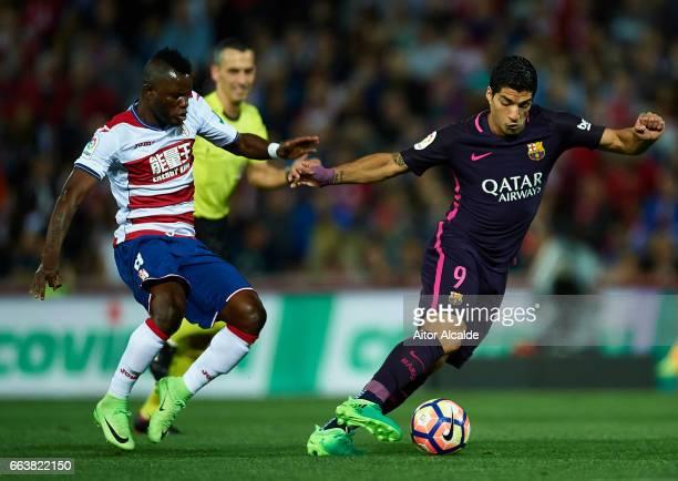 Luis Suarez of FC Barcelona being followed by Uche Wakaso Mubarak of Granada CF during the La Liga match between Granada CF v FC Barcelona at Estadio...