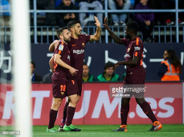 Luis Suarez of FC Barcelona celebrates with his teammate Jordi Alba and Samuel Umtiti of FC Barcelona after scoring the opening goal during the La...