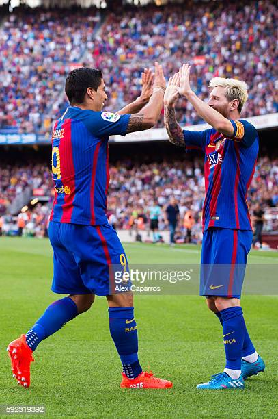 Luis Suarez of FC Barcelona celebrates with his teammate Lionel Messi after scoring his team's fourth goal during the La Liga match between FC...