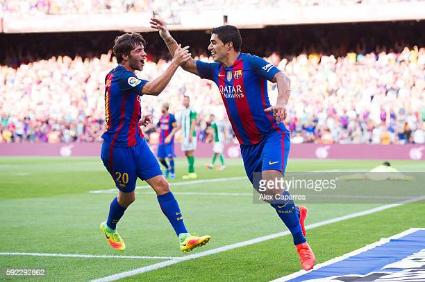 Luis Suarez of FC Barcelona celebrates with his teammate Sergi Roberto after scoring his team's third goal during the La Liga match between FC...