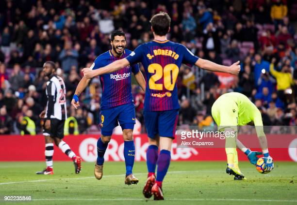 Luis Suarez of FC Barcelona celebrates with his teammate Sergi Roberto after scoring his sides second goal during the La Liga match between Barcelona...