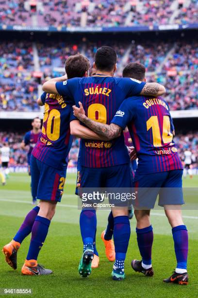 Luis Suarez of FC Barcelona celebrates with his teammates Sergi Roberto and Philippe Coutinho after scoring the opening goal during the La Liga match...