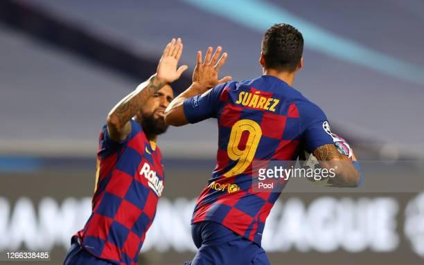 Luis Suarez of FC Barcelona celebrates with teammate Arturo Vidal after scoring his team's second goal during the UEFA Champions League Quarter Final...