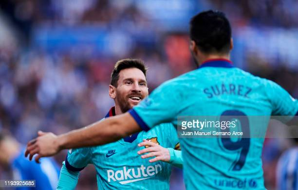 Luis Suarez of FC Barcelona celebrates with teammate Lionel Messi after scoring his team's second goal during the Liga match between Real Sociedad...