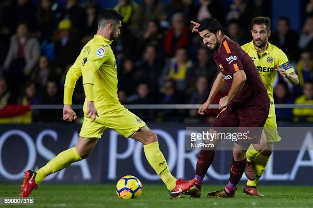 Luis Suarez of FC Barcelona competes for the ball with Alvaro and Mario Gaspar of Villarreal CF during the La Liga game between Villarreal CF and FC...