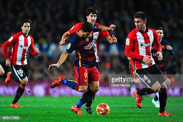 Luis Suarez of FC Barcelona competes for the ball with Aymeric Laporte and Mikel San Jose of Athletic Club during the La Liga match between FC...
