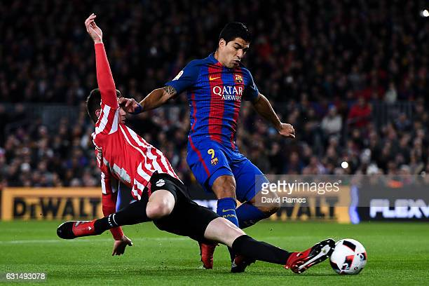 Luis Suarez of FC Barcelona competes for the ball with Aymeric Laporte of Athletic Club during the Copa del Rey round of 16 second leg match between...