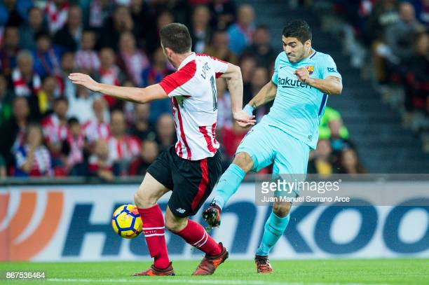 Luis Suarez of FC Barcelona competes for the ball with Aymeric Laporte of Athletic Club during the La Liga match between Athletic Club Bilbao and FC...