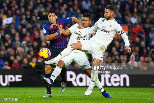 Luis Suarez of FC Barcelona competes for the ball with Carlos Enrique Casimiro and Sergio Ramos of Real Madrid CF during the La Liga match between FC...