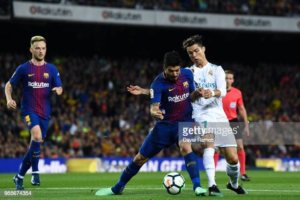 Luis Suarez of FC Barcelona competes for the ball with Cristiano Ronaldo of Real Madrid CF during the La Liga match between Barcelona and Real Madrid...