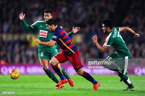 Luis Suarez of FC Barcelona competes for the ball with Eddy Silvestre and Mauro Dos Santos of SD Eibar during the La Liga match between FC Barcelona...