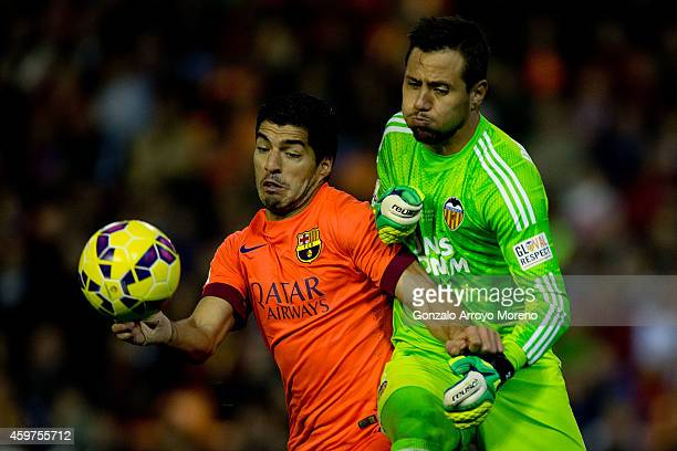Luis Suarez of FC Barcelona competes for the ball with goalkeeper Diego Alves of Valencia CF during the La Liga match between Valencia CF and FC...