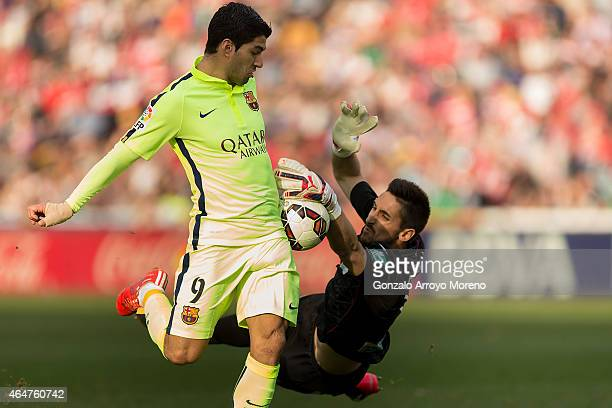 Luis Suarez of FC Barcelona competes for the ball with goalkeeper Oier Olazabal of Granada CF during the La Liga match between Granada CF and FC...