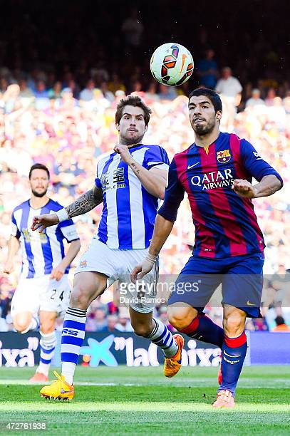 Luis Suarez of FC Barcelona competes for the ball with Inigo Martinez of Real Sociedad de Futbol during the La Liga match between FC Barcelona and...