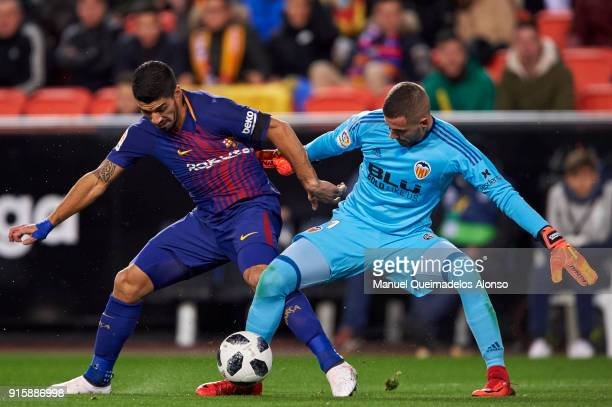 Luis Suarez of FC Barcelona competes for the ball with Jaume Domenech of Valencia CF during the Copa de Rey semifinal second leg match between...